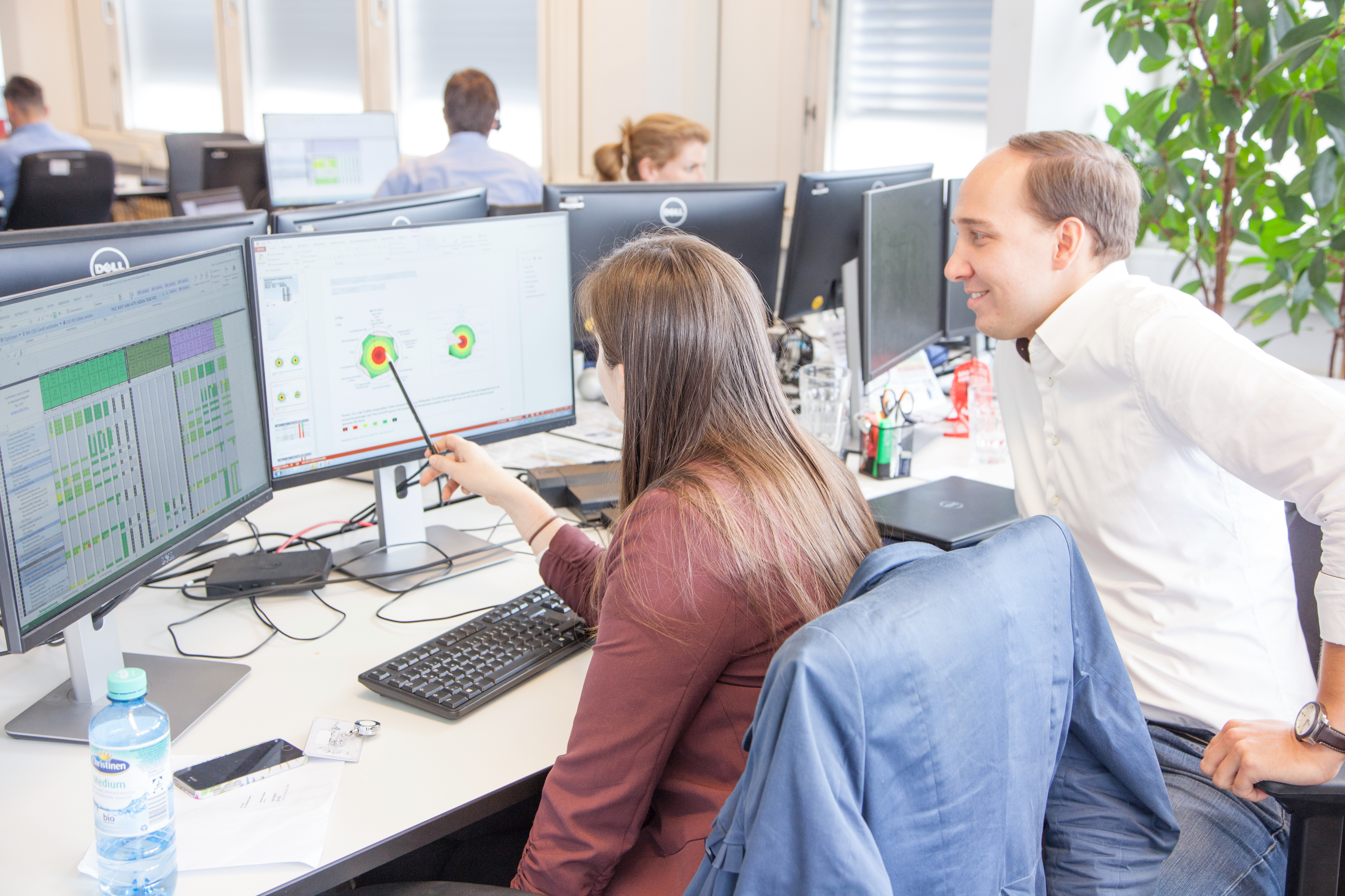 Zwei Mitarbeiter der VISPIRON SYSTEMS besprechen am Arbeitsplatz einen Qualitätsreport